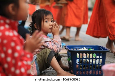 Luang Prabang , Laos 2018 April 14.A lot of monks walking bear foot in the morning, the girl and people feed into  monk's bowl at Luang Prabang,  World Heritage Site.Songkran Festival Happy new year