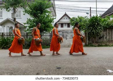 LUANG PRABANG, LAOS - 9/24/2017: Four Buddhist monks collect alms in Luang Prabang, Laos
