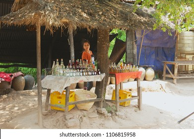 LUANG PRABANG, LAOS - APRIL 04, 2012: Unidentified lady sells bottles with locally produced rice alcohol in a street shop in Ban Xabg Hay village inn Luang Prabang, Laos.