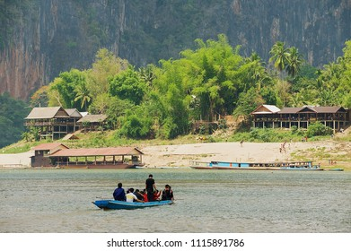LUANG PRABANG, LAOS - APRIL 12, 2012: Unidentified people cross river by boat at the confluence of the Mekong and the Nam Ou rivers in Luang Prabang, Laos.