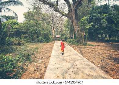 LUANG PRABANG, LAOS - April 2019: Buddhist monk walking through the forest in Luang Prabang, Laos