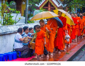 LUANG PRABANG , LAOS - AUG 11 2018 : Buddhist alms giving ceremony in Luang Prabang Laos on August 11 2018. It is estimated that about 1 in 3 male Laotians join a monastery