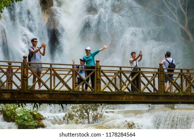 LUANG PRABANG, LAOS - August 12,2018 : People on bridge looking and take photo with viewpoint of Kuang Si Falls or Tat Kuang Si Waterfalls on August 12,2018 in Luang Prabang, Laos