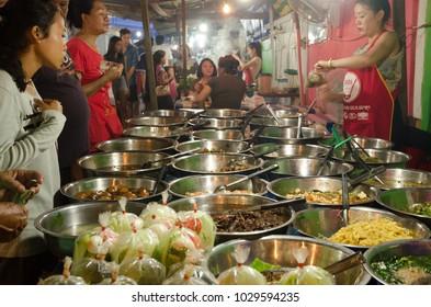 LUANG PRABANG, LAOS - AUGUST 16 2017: Women is selling local food during night market in Luang Prabang.