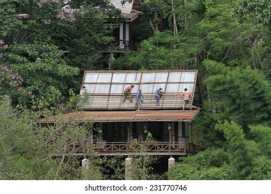 LUANG PRABANG, LAOS - AUGUST 16: Local workers fixing a roof on a building on the banks of the Mekong River in Luang Prabang, Laos on the 16th August, 2014.