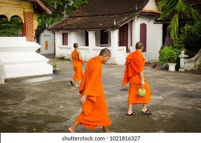 LUANG PRABANG, LAOS - AUGUST, 2017 : Monks walking in the street at Luang Prabang town on August 17th 2017.