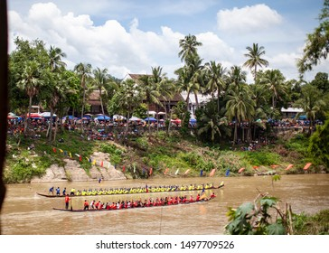 Luang Prabang, Laos - August 29, 2019 - Annual Dragonboat race held on the Mekong River with fans and onlookers watching from the riverbank