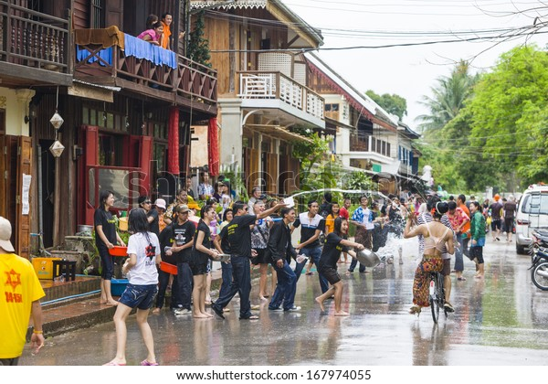 LUANG PRABANG, LAOS - CIRCA APRIL 2011 - Local people throw water on each other as part of the Phi Mai or New Year festival, circa April 2011, in Luang Prabang, Laos