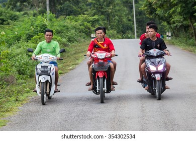 Luang Prabang, Laos - circa August 2015: Boys driving motorbikes outside Luang Prabang, Laos