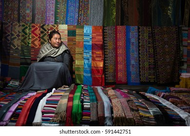 LUANG PRABANG, LAOS - DEC 16, 2013: Woman sits in her stall at night market, selling scarves.