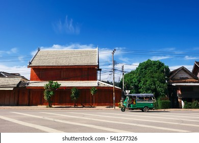 LUANG PRABANG, LAOS - DECEMBER 05 2016: Driving tuk tuk on the road of Luang Prabang town.