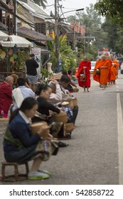 Luang Prabang, Laos - December 22, 2016: The morning alms ceremony sees monks collect food offerings from local people in Luang Prabang.  This happens each day just as the sun begins to rise.