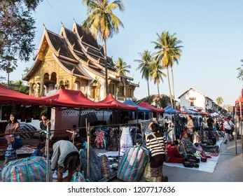 Luang Prabang, Laos - January 23, 2018: The famous night market of Luang Prabang, Laos. In the background is the Royal Palace Temple