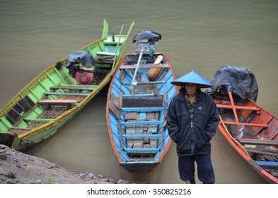 LUANG PRABANG, LAOS - JANUARY 5, 2017: The longtail boats and the fisherman who is a local guide for lead traveling at Khong river , Laos