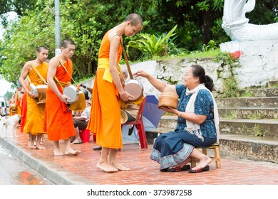 Luang Prabang, Laos - Jun 12 2015: Buddhist alms giving ceremony in the morning. The tradition of giving alms to monks in Luang Prabang has been extended to tourists.