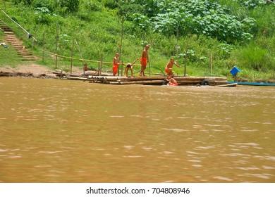 LUANG PRABANG, LAOS, JUNE 25, 2016 : The children novice buddhist monks playing happily on the Mekong river in Luang Prabang, Laos