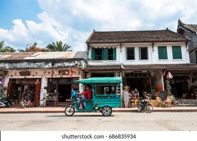 LUANG PRABANG, LAOS - MARCH 11, 2017: Horizonal picture of restaurants and stores at Sisavangvong Road, located in the olf Quarter of Luang Prabang, Laos. Tuk tuk  and motorcycles.