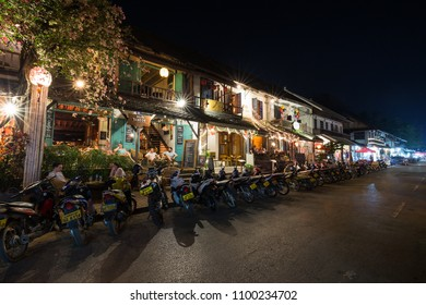 Luang Prabang, Laos - March 21, 2018: Parked scooters and people sitting in lit French colonial era buildings which are converted into restaurants on idyllic Sisavangvong Road in Luang Prabang, Laos.