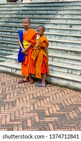 Luang Prabang, Laos - March 23, 2019 :  Young monks on steps Royal Museum in Luang Prabang, Laos.
