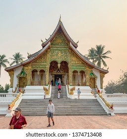 Luang Prabang, Laos - March 23, 2019 :  Tourists on steps of temple, or wat, on grounds of Royal Museum in Luang Prabang, Laos.