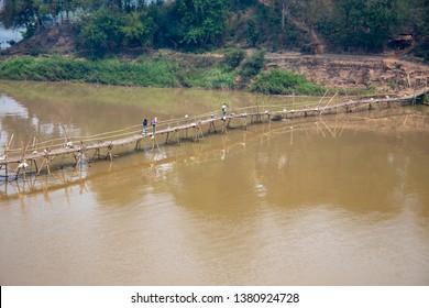 Luang Prabang, Laos - March 23, 2019 :  Tourists walking over bamboo bridge over Nam Khan River in Luang Prabang, Laos.