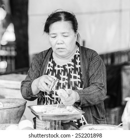 LUANG PRABANG, LAOS - SEP 25, 2014: Unidentified Lao woman works at the market. 55% of Laos people belong to the Lao ethnic group