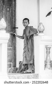 LUANG PRABANG, LAOS - SEP 25, 2014: Unidentified Lao buddist boy near a door. 55% of Laos people belong to the Lao ethnic group