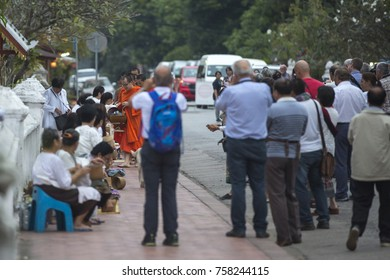 Luang Prabang, Loas - November 19, 2017: Torists taking photos of buddhist monks on everyday morning traditional alms giving in Luang Prabang, Laos.