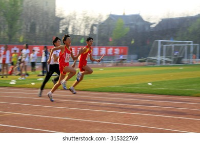 LUANNAN COUNTY - APRIL 14: 400 meter relay runner at the sports meeting, April 14, 2015, Luannan County, Hebei Province, China
