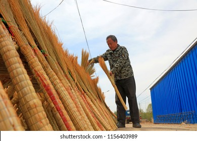 Luannan County - April 24, 2018: worker air drying brooms out of the workshop, Luannan County, Hebei Province, China