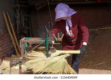 Luannan County - April 24, 2018: worker processing the broom in the workshop, Luannan County, Hebei Province, China
