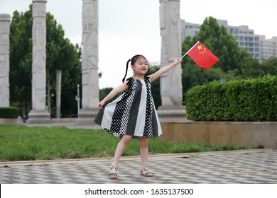 Luannan County, China - July 11, 2019: A little girl waved the Chinese flag in the park, Luannan County, Hebei Province, China