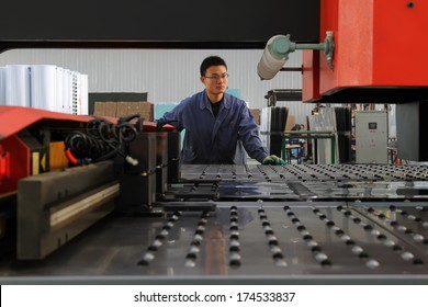 LUANNAN COUNTY, CHINA - NOV 24, 2012: A worker was operating CNC machine tools, in the DingRe Solar Energy Ltd, in November 24, 2012, Luannan County, china.
