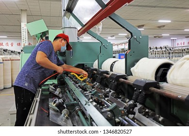 Luannan County - December 17, 2018: Technicians maintain machinery and equipment in the spinning mill, Luannan County, Hebei Province, China