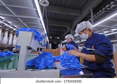 LUANNAN COUNTY - February 2, 2020: women workers busy in the production line of nitrile protective gloves, LUANNAN COUNTY, Hebei Province, China