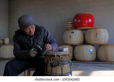 Luannan County - February 6, 2018: craftsman is working on the drum in workshops, Luannan, Hebei, China