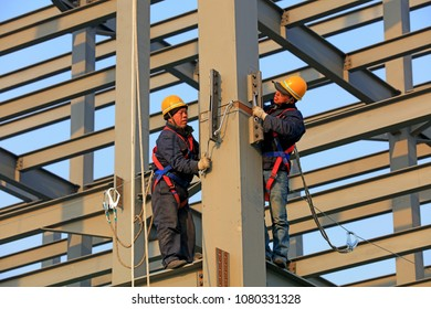 Luannan county - March 22, 2018: workers work on steel girders in a construction site, luannan county, hebei province, China.