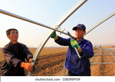 Luannan county - March 22, 2018: workers are building an oval tube full steel greenhouse greenhouse, luannan county, hebei province, China.
