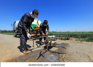Luannan County - May 21, 2019: Workers cleaning agricultural UAV nozzles on the farm, Luannan County, Hebei Province, China