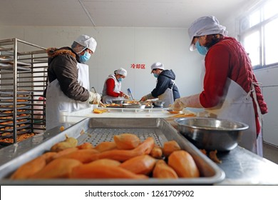 Luannan County - November 23, 2018: Workers cut sweet potatoes in production workshop, Luannan County, Hebei Province, China