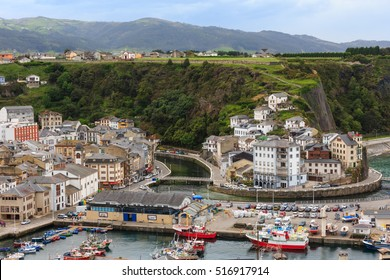 LUARCA, SPAIN -  MAY 10, 2016: Evening Luarca cityscape (top view) with colorful boats in fishing port, Asturias, Spain.