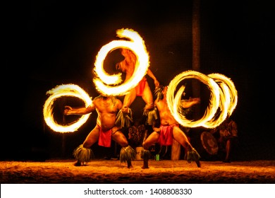 Luau hawaiian fire dancers motion blur tourist attraction in Hawaii or French Polynesia, traditional polynesian dance with men dancer.