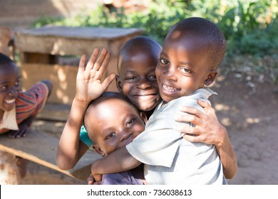 Lubanyi, Buikwe, Uganda. 28 April 2017. A group of three happy (3) little boys - brothers - hugging each and one of them is waving at the camera.