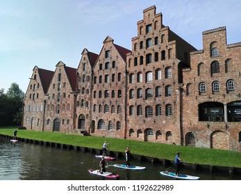 Lubeck city, Germany 23 Sep 2017; The family of surfing boat on Embankment of the river Trave and Museum Holstentor & Medieval typical crow stepped gabled town house. Heritage Site World.