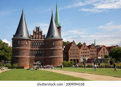 Lubeck, germany - August 12, 2018.  Holstentor gate with blue sky, clouds and people walking around in the green grass.