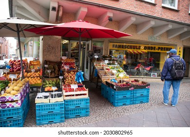 lubeck, germany - August 14, 2018. A man looks at produce in a fresh air market in downtown Lubeck, Germany.  Blue stands with colorful fresh produce and a buyer looking at it.