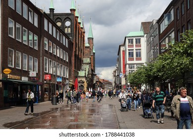 Lubeck, Germany - July 3, 2019: People walking in Breite strasse shopping street along the city hall and other historical buildings in Lubeck, Germany on July 3, 2019