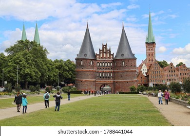 Lubeck, Germany - July 3, 2019: People walk in the small park in front of the Holstentor gate in Lubeck, Germany on July 3, 2019