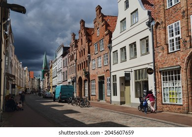 Lubeck, Germany - July 3, 2019: People walking in a shopping street with historical buildings under a cloudy sky in Lubeck, Germany on July 3, 2019