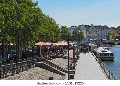 LUBECK, GERMANY - MAY 25, 2018: cafes with tourists on the bank of the trave river in the old town of lubeck, germany